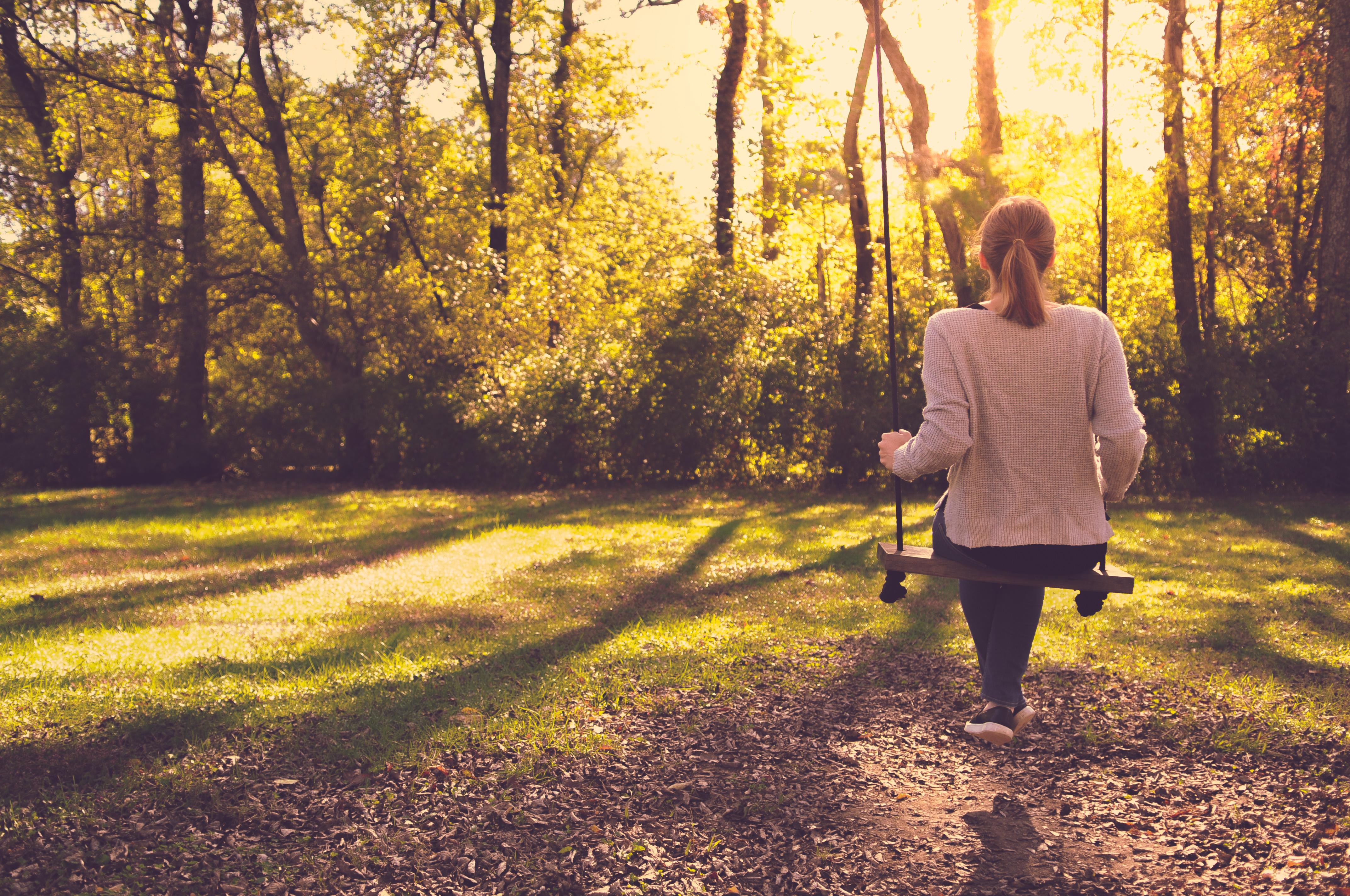 Girl Sitting Alone On Swing In Autumn